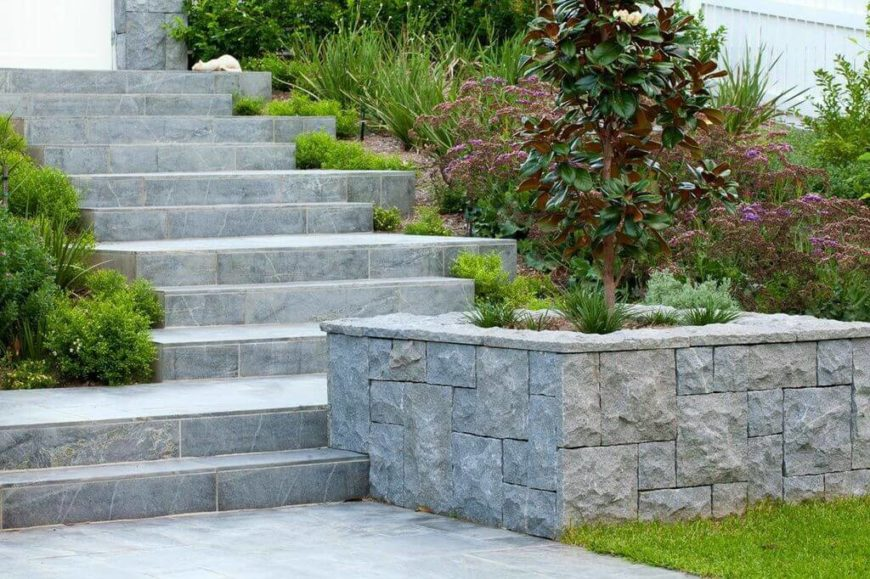 A close up on the steps and stone planters reveals the way the planters are merged into the stone steps. Small veins in the stone of the steps creates an artificial aging effect.
