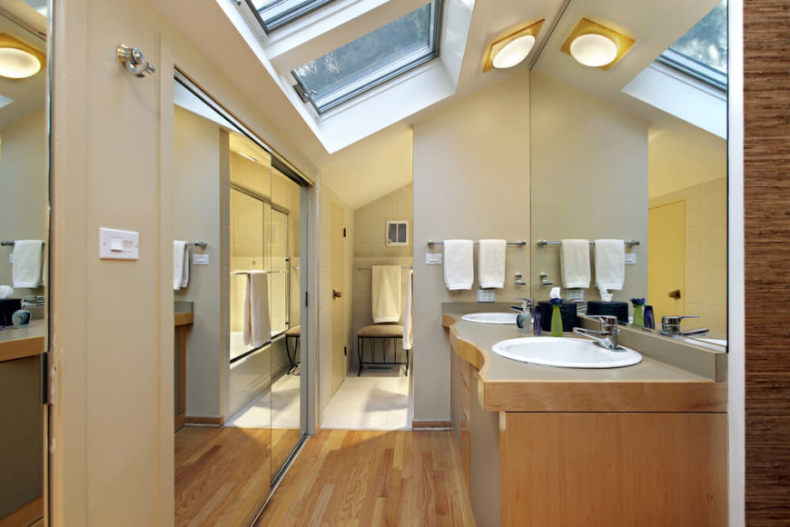 Gorgeous skylights are reflected in the large mirror above the double vanity, maximizing daylight and opening up this small space. Natural hardwood floors lead into the main bathing area, while beige walls offer a neutral backdrop allowing the mirrored walls to take center stage.