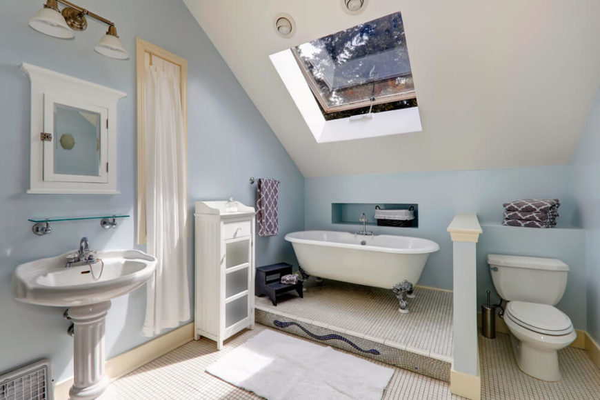 This charming bathroom features an extravagant clawfoot tub, painted white cabinetry, a traditional pedestal sink, and a beautiful mosaic at the base of the bathing area. A skylight allows healthy rays to filter through to brighten the powder blue and white space.