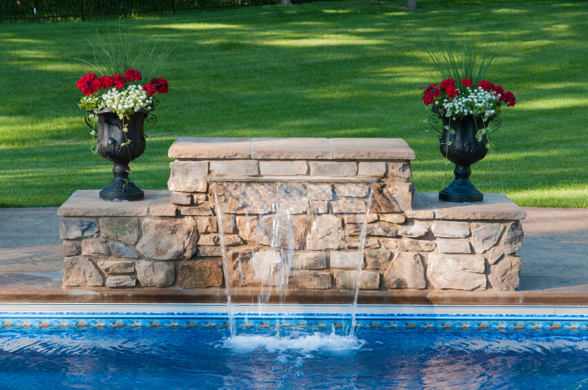 An elegant stone fountain with urns on either side. All the machinery needed is hidden inside the stone enclosure.