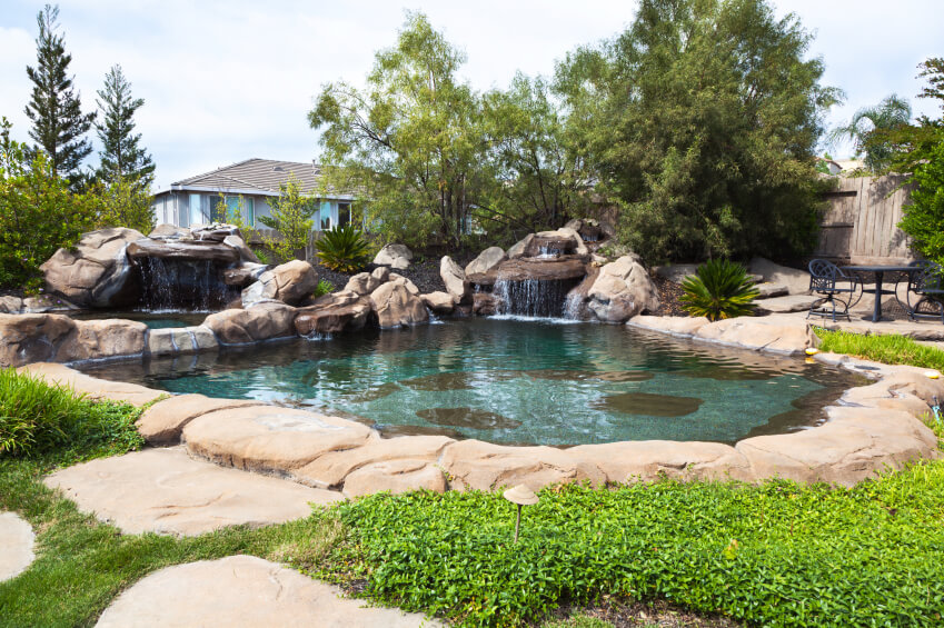 A swimming pool with two waterfalls and darker patches of stone on the bottom to give it a natural look.