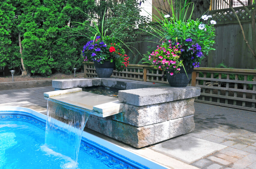 A contemporary fountain with a small reservoir that contains a few small goldfish.