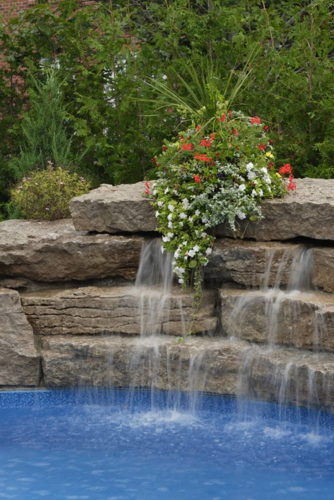 A neatly arranged artificial waterfall that cascades down into the in-ground pool. A flower arrangement on the top stone drapes down in harmony with the water.