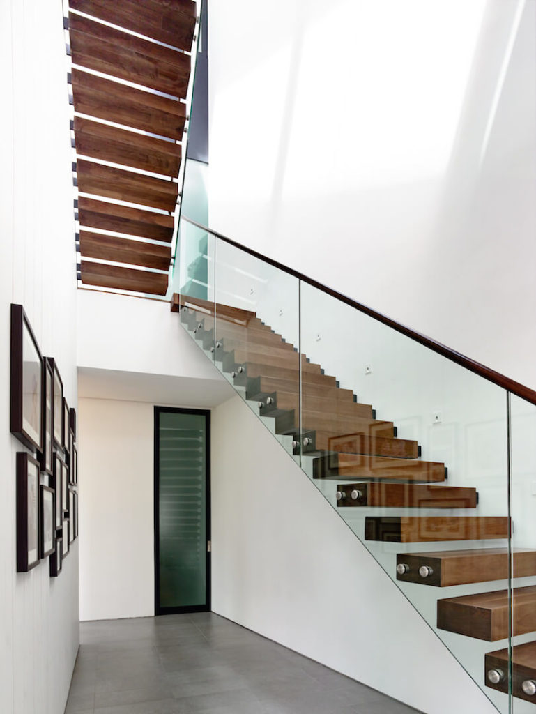 """The home's entryway opens up immediately into the cantilevered """"floating"""" staircase with glass sides and a wooden railing. A narrow frosted glass door opens up into a closet area. Along the left wall, an arrangement of family photographs welcomes visitors into the home with smiles."""