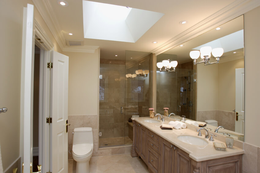 Mirror Sconces Recessed Lighting And A Skylight Work Together To Highlight This Lovely Bathroom