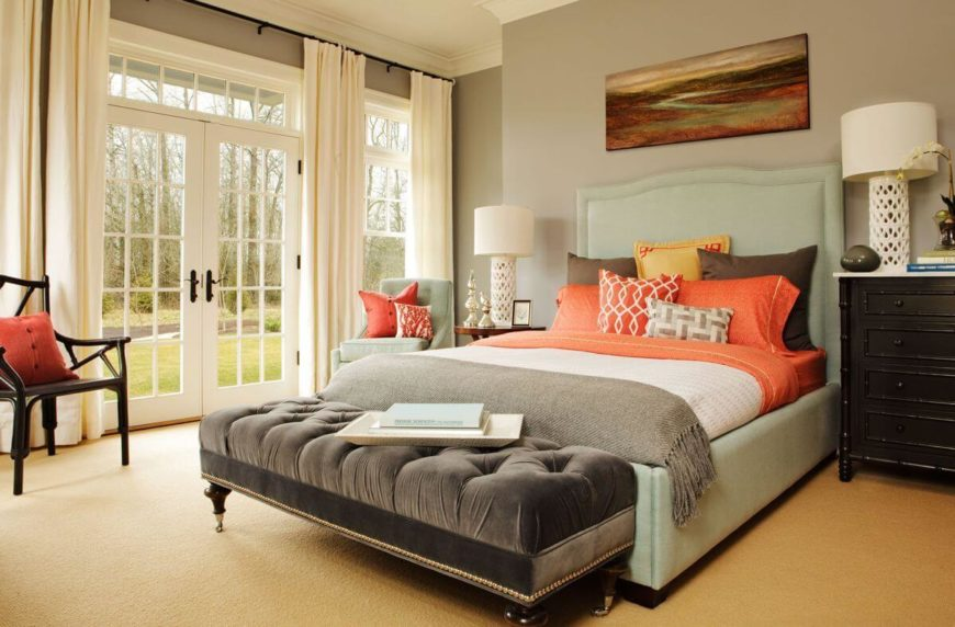 The main floor is host to the guest bedroom, which has French doors that lead out into the backyard. The pale mint upholstered bed is topped by bedding of various colors including gray, brown, white, and peach. The enormous button-tufted bench at the foot of the bed has nailhead trim all along the bottom.
