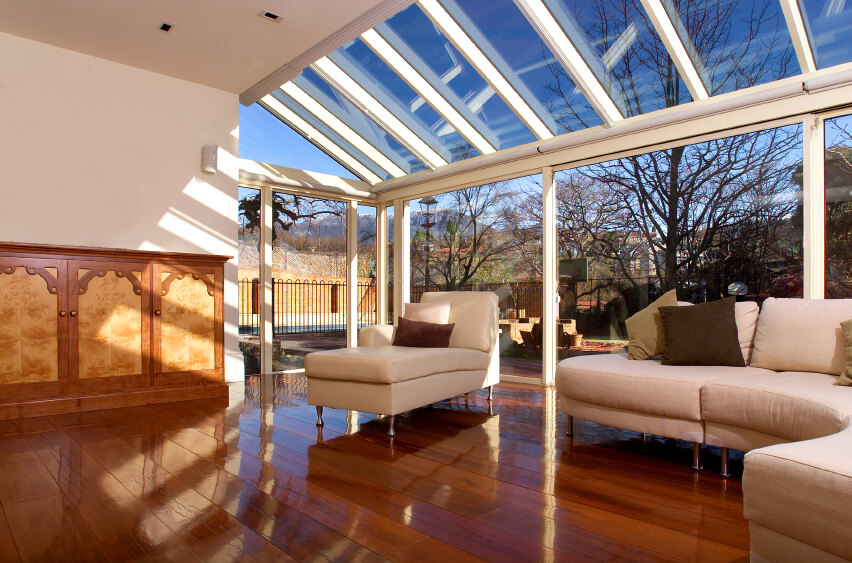 This outstanding room features glazing that leads right up into angled skylights. The dark hardwood floors are given a glossy finish under the pure sunlight in this open living room.