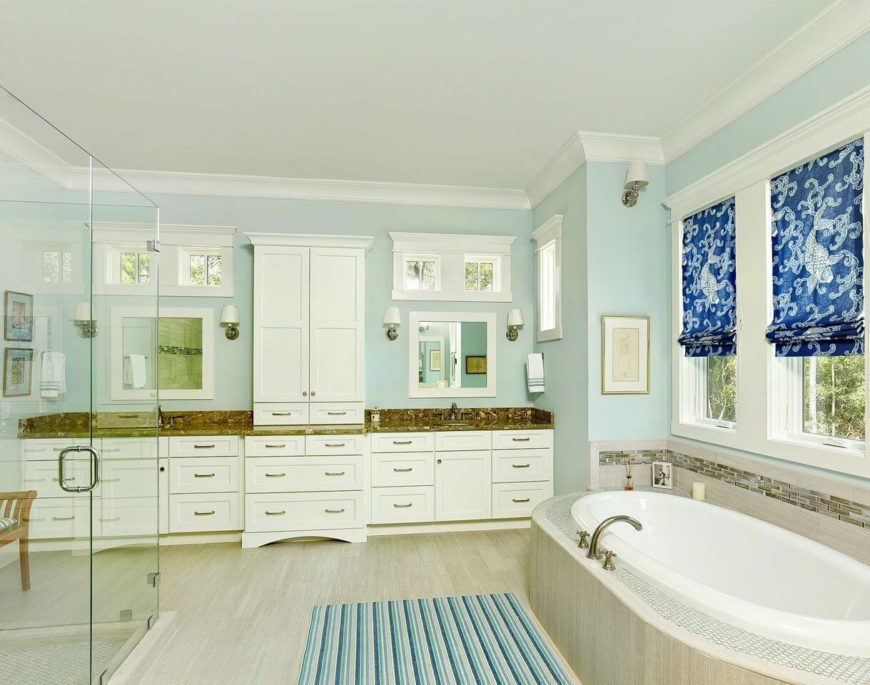 The master bathroom has an enormous glass-enclosed shower, a soaking tub beneath the windows, and a dual vanity on either side of a towel cabinet.