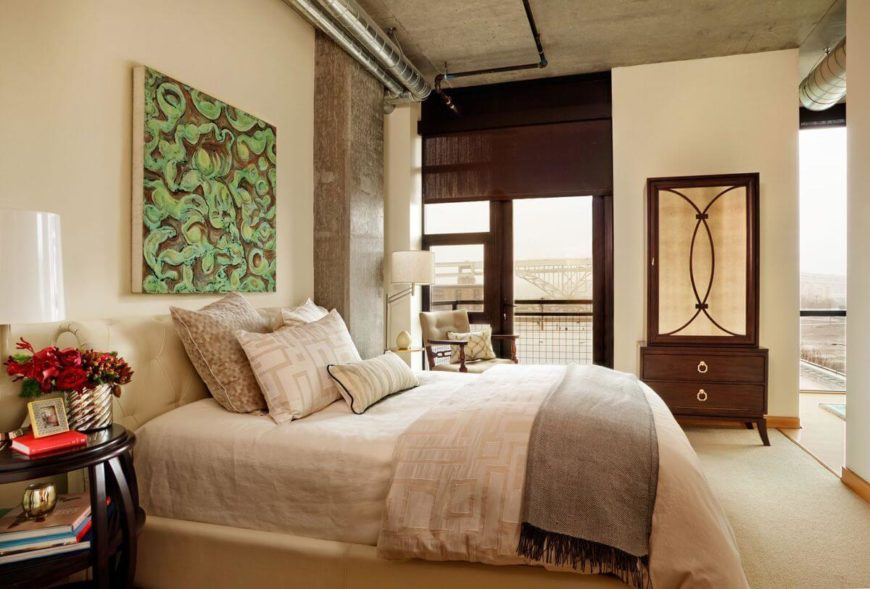 The master bedroom also has access to the balcony and an ensuite bathroom. Like the other bedroom, this one has a piece of modern art behind the bedroom. The elegant wardrobe on the far wall has a mirrored front.