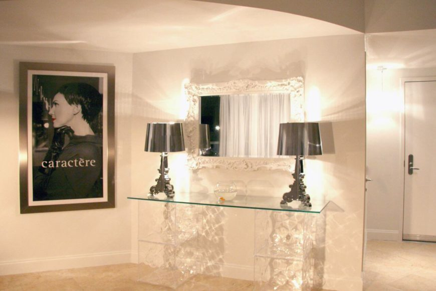 The entryway to the home is characterized by the sleek glass topped table with matching chrome lamps. An ornate mirror painted white hangs above the table. To the left is a portrait.