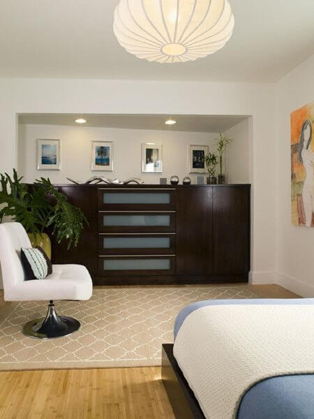 A view from the nightstand to the inset enormous dresser on the far side of the room. The light fixture is shaped like an extended paper lantern. The very contemporary beige rug between the dresser and the bed has a single armless chair.