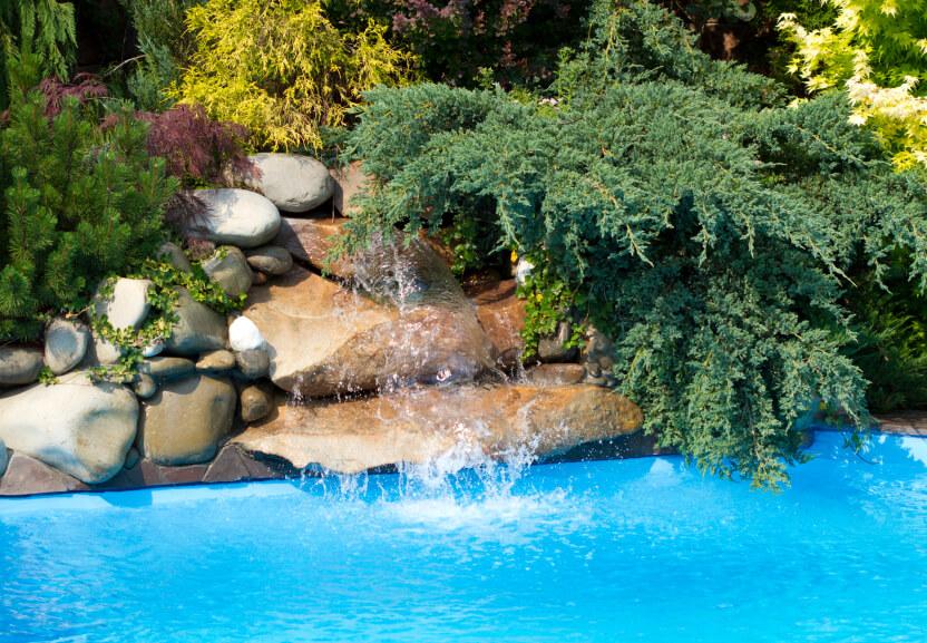 A smooth stone waterfall hidden partially underneath an evergreen.