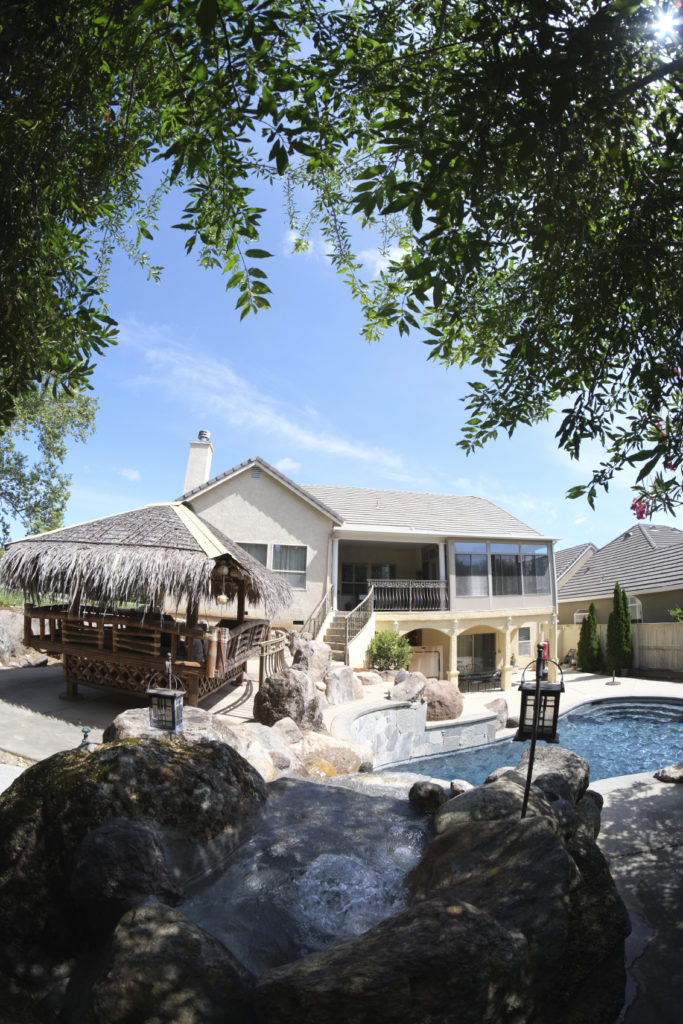 A pool oasis with a raised palm-roof gazebo and a large artificial stone waterfall pouring into the figure-eight pool.