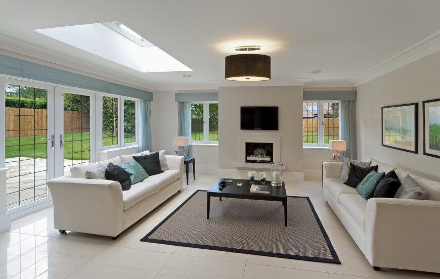 This living room has an asymmetrical ceiling, with a skylight on only one side of the room. The modern color scheme coordinates with the peaceful warmth of the skylight.