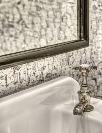 A close up in the bathroom of the antiqued nickel faucet and the contemporary wallpaper.