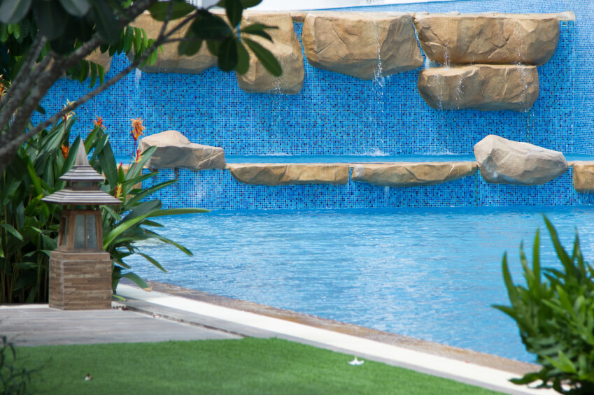 A unique swimming pool with an enormous mosaic tile wall and multiple ledges that act as a waterfall.
