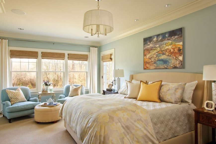 The master bedroom has an enormous upholstered bed with bronze nailhead trim and a subtle floral pattern on the bedding. Natural fiber roman shades cover the windows at nighttime. Near the windows is a seating area with two plush armchairs and a circular ottoman.