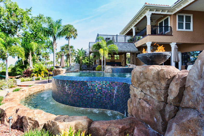 An infinity pool with a glossy glass mosaic tile waterfall that pours into a small reservoir pool surrounded by natural stones.