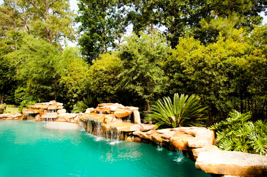 A swimming pool surrounded by layered stones with several waterfalls around the edges.