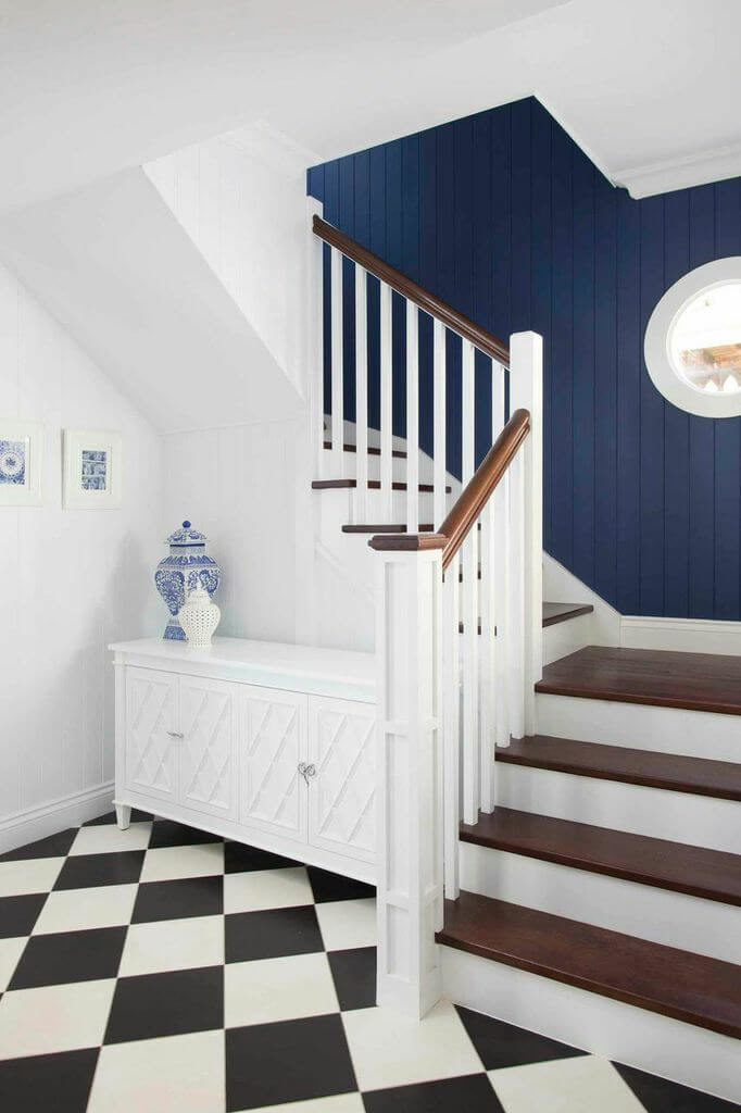 The foyer is a pristine white with a checkerboard tile floor. Immediately to the right of the front door is a staircase leading up to the second floor. A rich blue on the clapboard walls going up the stairs is accented by beautiful Delft blue pottery and prints in the main entryway.