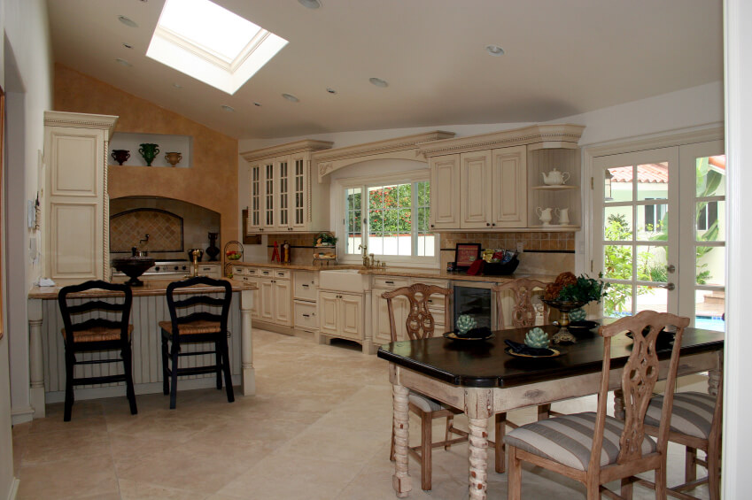 This country kitchen has amazing wooden cabinets and drawers, with a rustic polished look to them. An angled skylight brings in a natural illumination to the various hues and tones of this fantastic room.