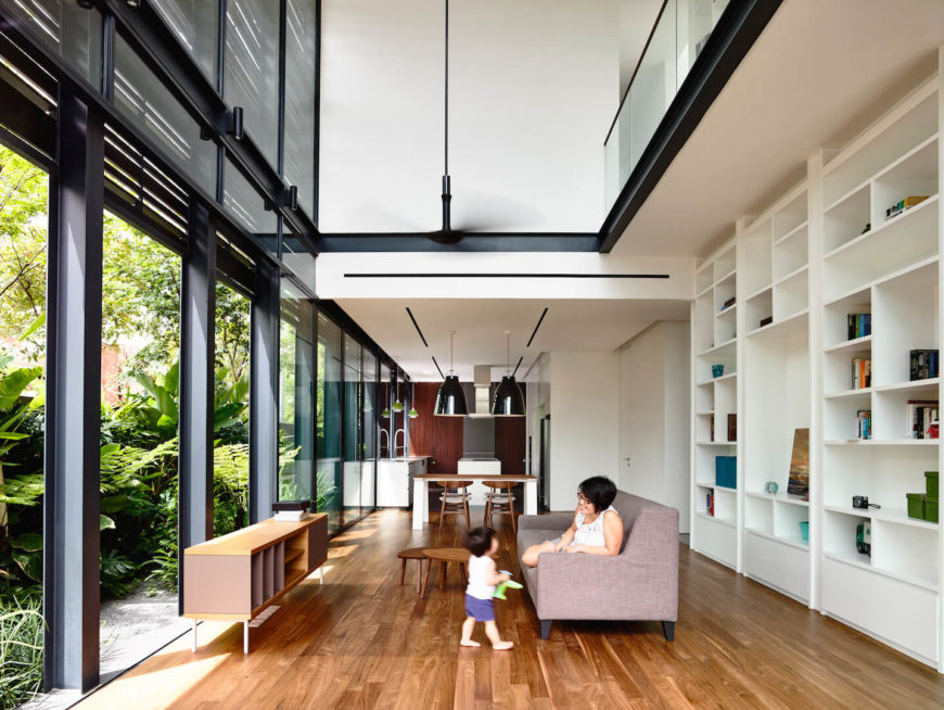 A view of the lengthy living room with floor-to-ceiling windows and cathedral ceilings. At the back of the space is the sleek, small kitchen in white and rich wood. To the right is a built-in bookcase with shelves of varying heights and sizes and pull-out drawers beneath.