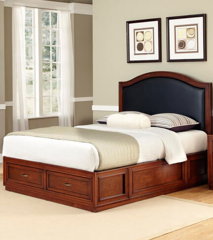 A cherry-finished wooden frame with an embossed leather panel inset that is padded for extra comfort. The two drawers in the footboard have antiqued brass hardware.
