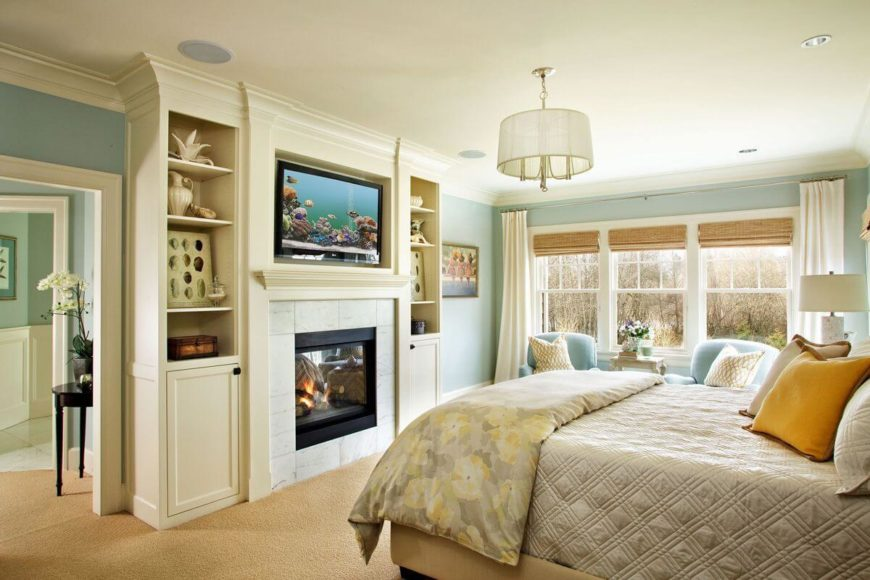 A view of the master bedroom's built-in shelving next to the glass-enclosed fireplace that is topped by an inset television. A short section of hallway rests between the master bedroom and the adjacent bathroom.