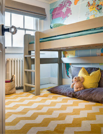 A second child's room with a yellow chevron rug and an elevated bed with a snuggle nook below. The wall behind the bed is an accent wall with a map of the world.