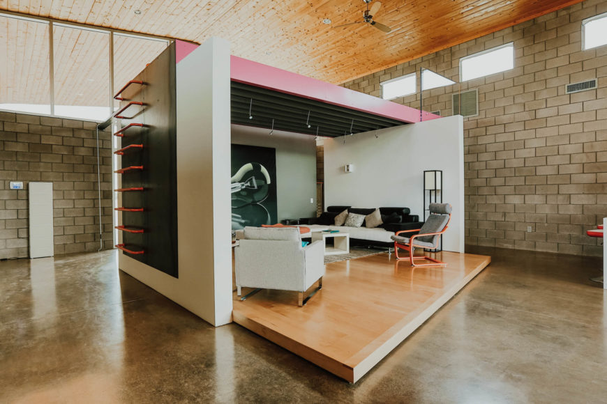 """Here we see the """"stage for living,"""" a three-walled room secluded in the center of the open space. Raised platform wood flooring and steel beam ceiling frame the space, with a ladder on the side for easy access to the upper level."""