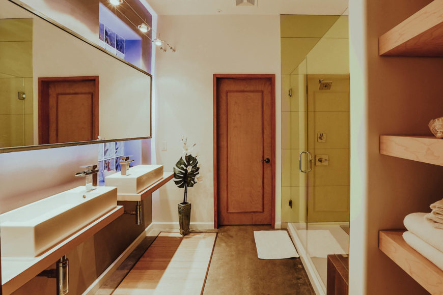 This bathroom, one of a handful of discrete, enclosed areas within the home, features light tones and a variety of contemporary details. Twin vanities with vessel sinks float below a wide singular mirror at left.