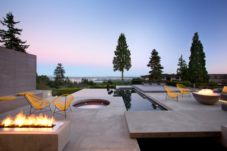 The patio features several distinct conversation and fire spaces featuring spectacular views. The pool is framed with an infinity edge, with a built-in jacuzzi seen at center.