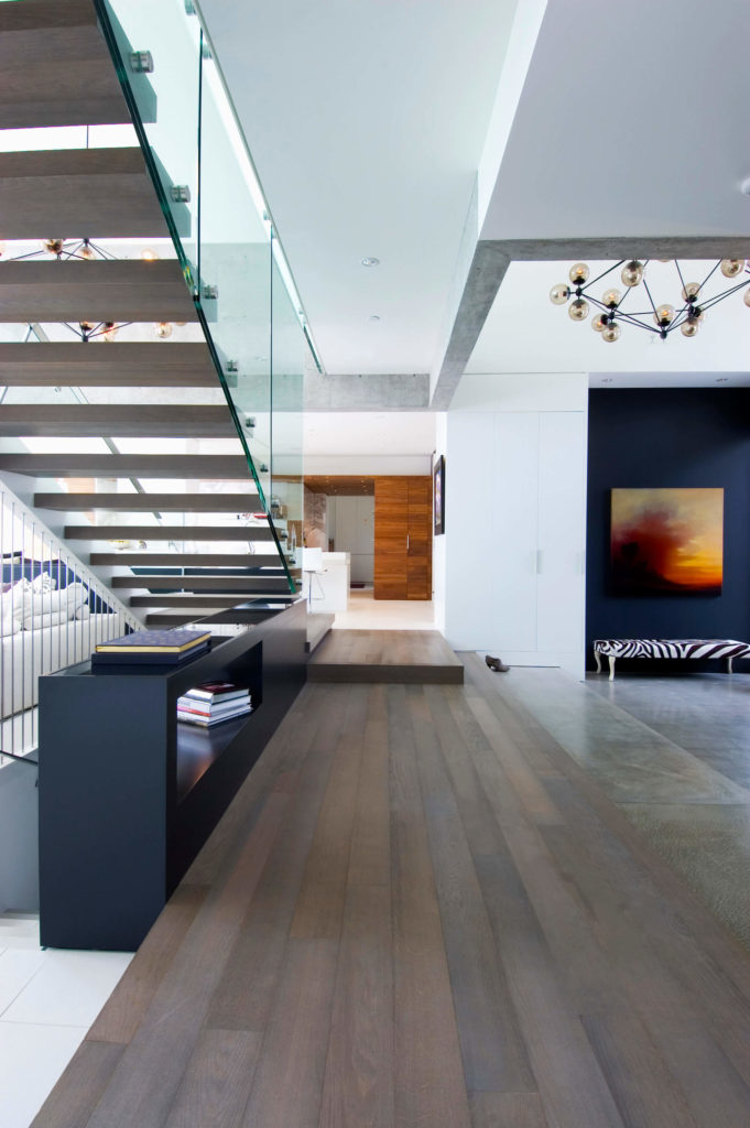 The central hall in the home is filled with hardwood flooring, bisecting the stone and white tile spaces of the interior. Central staircase is wrapped in glass panels, ensuring clear lines of sight throughout.