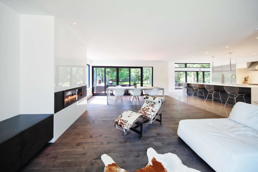 Here's the expansive central open-plan room. The large space comprises a living room area, full dining, and lengthy kitchen as seen at right. An expanse of rich natural wood flooring contrasts with the pristine white walls.