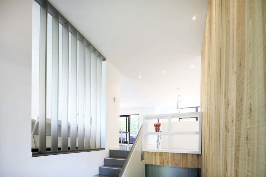 Entering the home, one goes up half a flight of stairs to the main open room. Light hued natural wood lines the right wall and stair area in contrast with the minimalist white upper level.