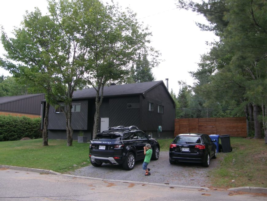 Here's the home before any work was done. The singular dark hued structure is box-like, with few windows, leading to an insular and closed-off appearance. The driveway is a simple gravel rectangle.