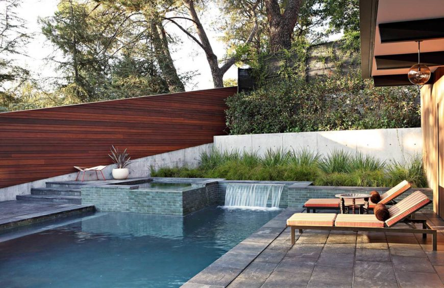 The tile wrapped pool features a small waterfall feature and raised jacuzzi, standing below the tall, sloped fence wrapping the property.