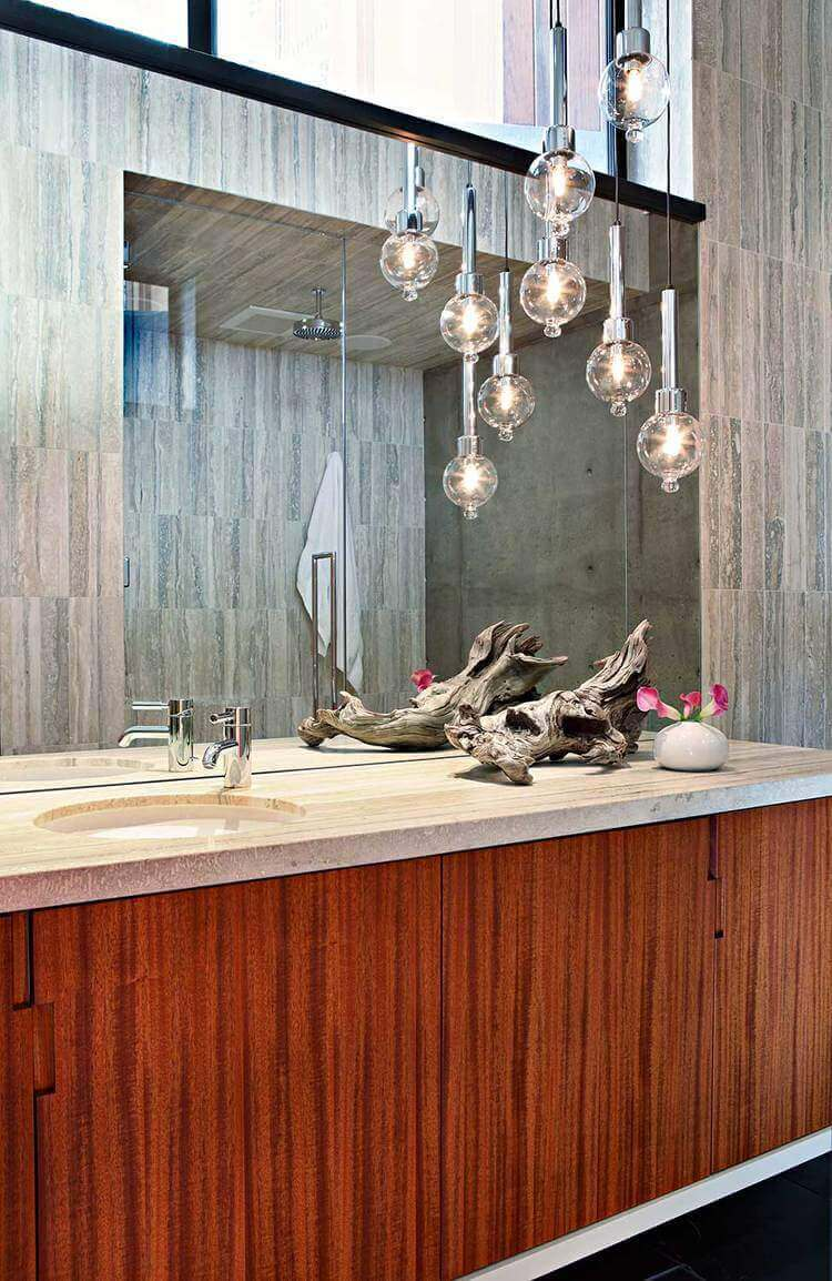 A focused shot at this mid-century master bathroom's sink counter with a very attractive decoration along with classy pendant lights.