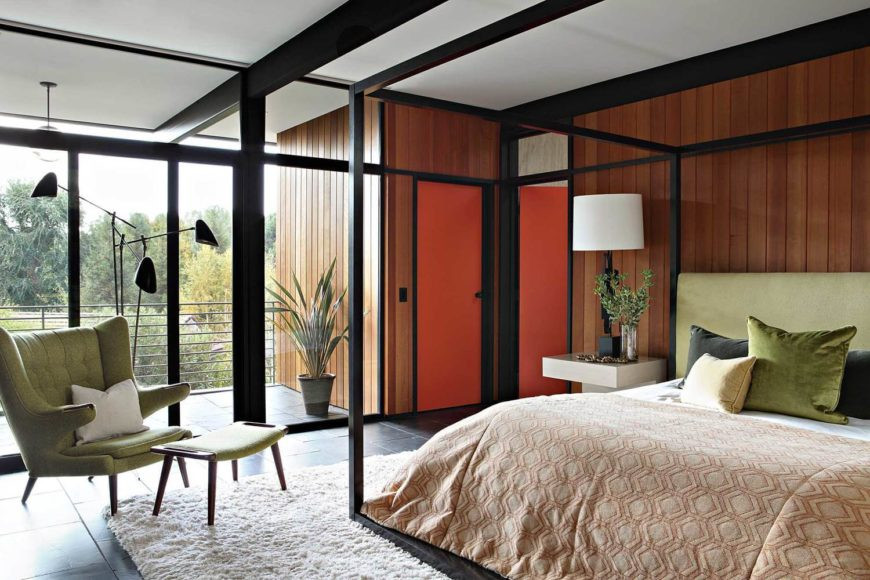 The master bedroom houses a large four-poster bed with a black metal frame matching the structure of the house. A small private balcony extends through full height glass at left.