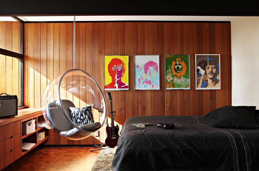 This room features an artful mixture of eclectic elements for the music lover, including Beatles art prints on the wall and a hanging, transparent egg chair. Built-in shelving matches the rich wood wall tones.