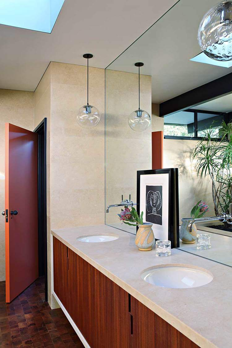 A master bathroom in mid-century style featuring a double sink lighted by pendant lights.