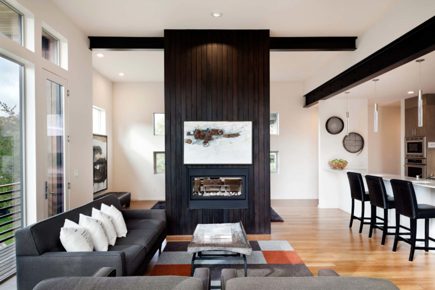 The large central chimney unites the entire structure, appearing with a two-sided fireplace in the open plan living space here. The kitchen and dining rooms share this area.
