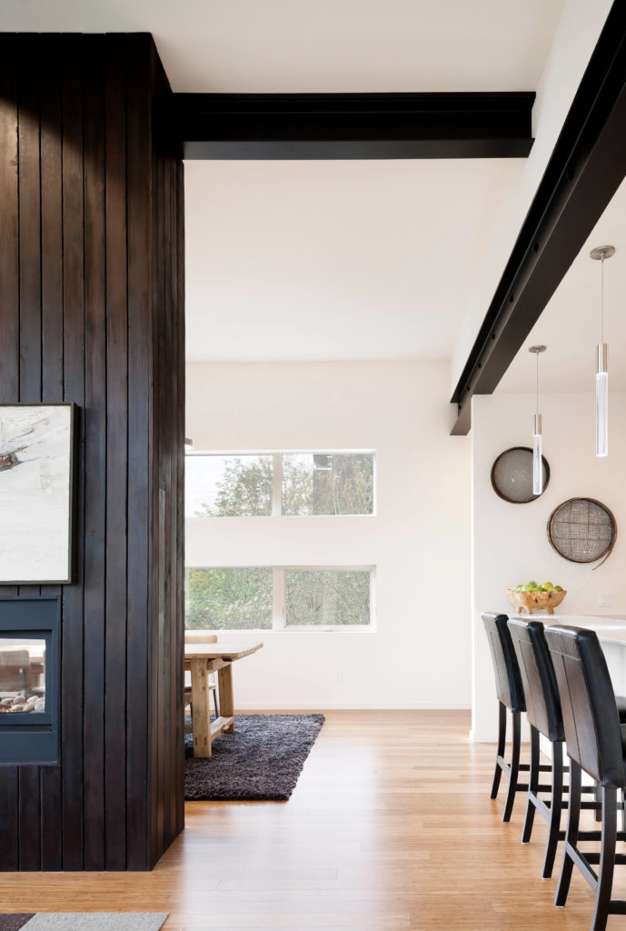 Peering around the fireplace, we see the bright hardwood flooring wrapping around toward a set of large horizontal windows and the dining table. Black leather bar stools line the counter at right.