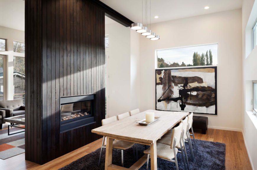 This part of the open space centers on a weathered wood dining table over a dark shag area rug. Modern touches, like the disc-like pendant lights and metal frame seating, add an interesting contrast.