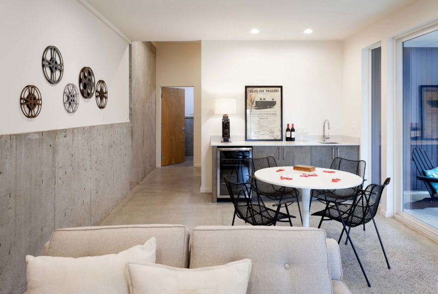 This family room on another level features a small dining set and countertop with sink and wine cooler. Concrete structural walls meet white surfaces for a neutral, light look.