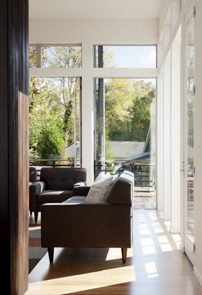 This cozy space includes contemporary dark brown sofas and chairs, matching the burnt wood look of the exterior and chimney. The wraparound balcony can be seen through full height glass.