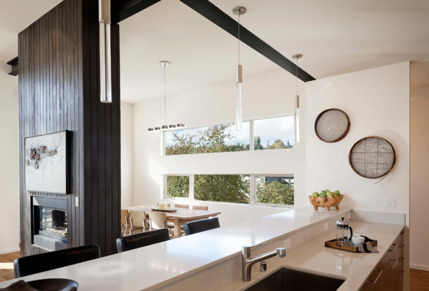 Viewed from the kitchen, we see sleek white countertops and cabinetry with contemporary hardware, with modern lighting throughout. Black I-beams add contrast and support throughout.