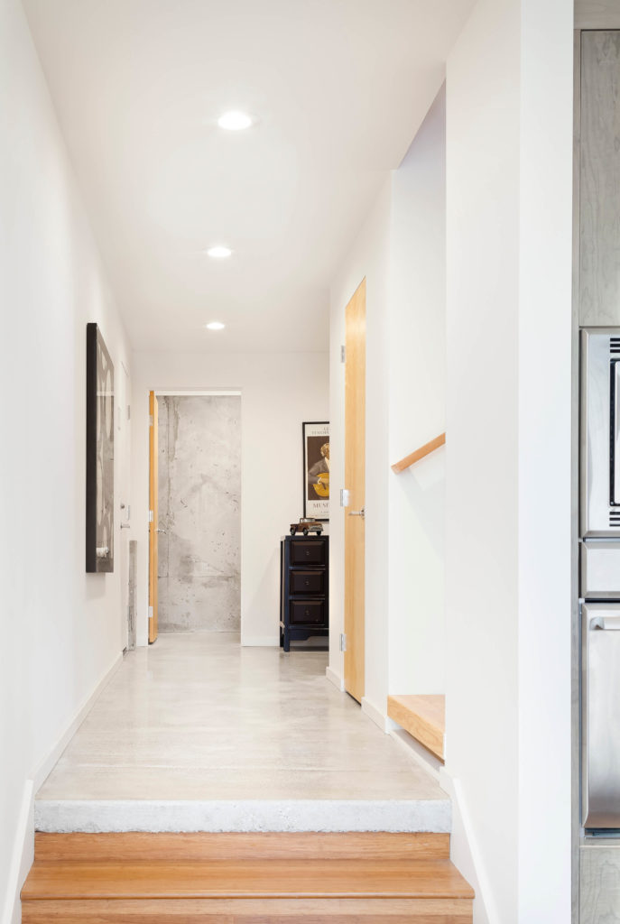 Next to the kitchen we see the hall, with stairs lading up and down in hardwood panels meeting on a polished concrete floor.