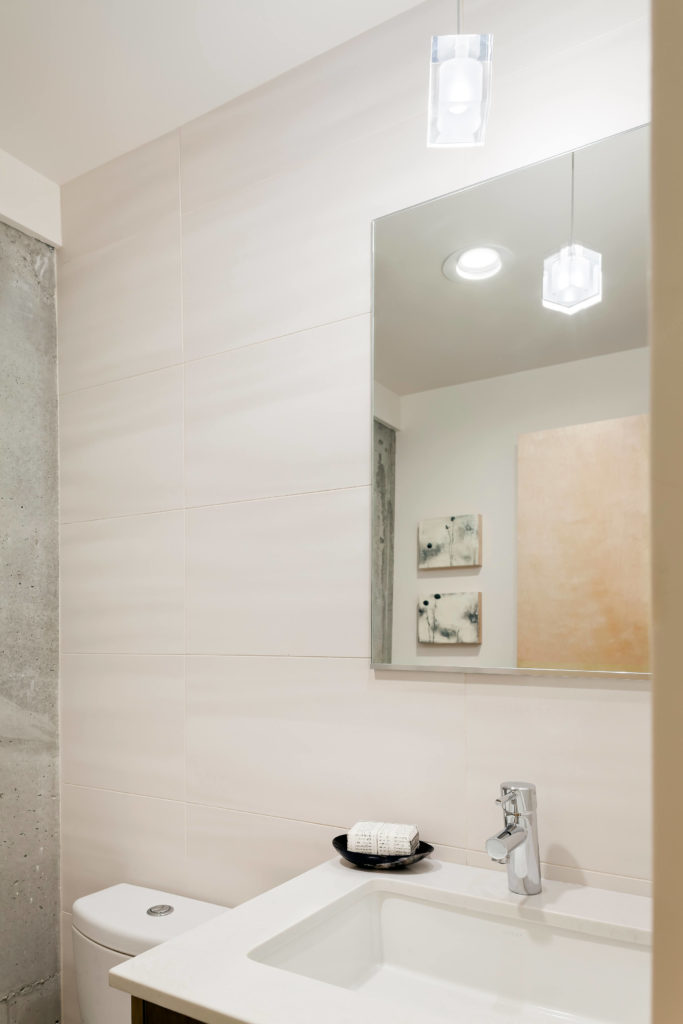 Bathroom continues the bright mixture of white and grey tones, with large format wall tiling meeting concrete in this corner.