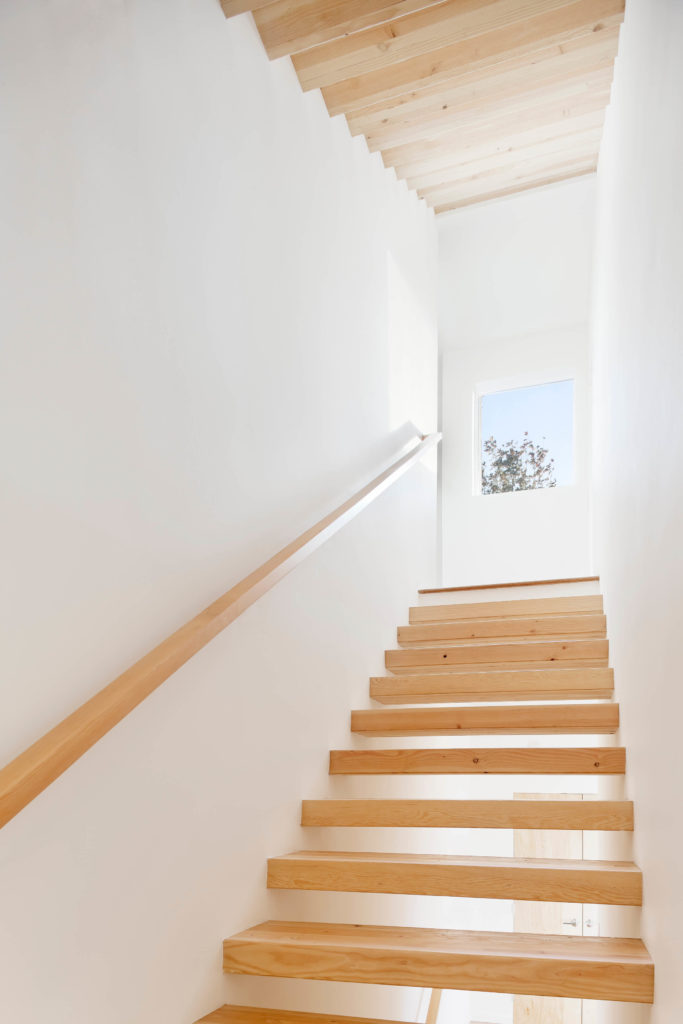 The floating stair design creates a perfect contrast with these light natural planks against white surroundings.